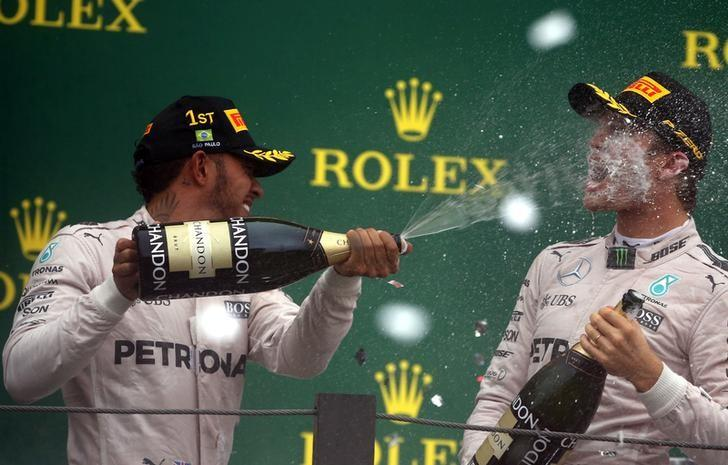 Formula One - F1 - Brazilian Grand Prix - Circuit of Interlagos, Sao Paulo, Brazil - 13/11/2016 - Race winning Mercedes' driver Lewis Hamilton of Britain (L) and teammate and second placed finisher Nico Rosberg of Germany spray champagne during the victory ceremony after the race. REUTERS/Paulo Whitaker